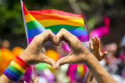 Pride flag (rainbow colours) with two hands in front of it. The hands are shaped into a heart.